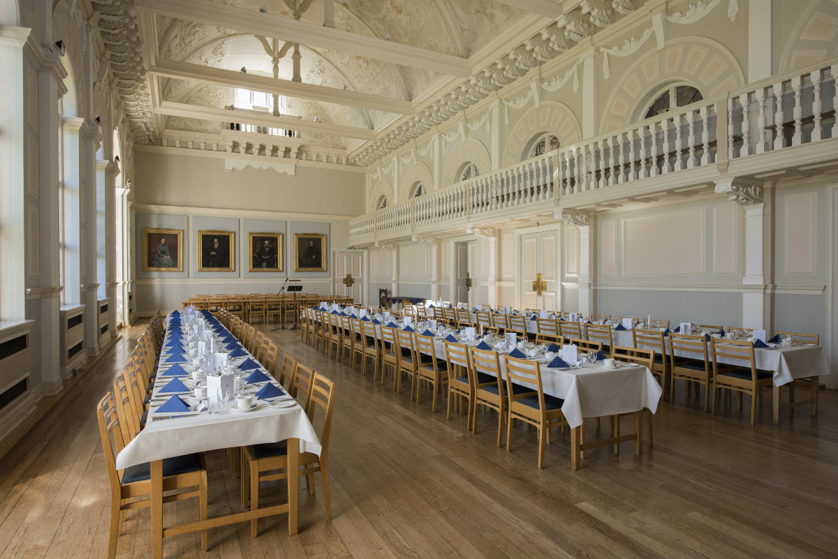 A photo of the College Hall set up for a banquet, showing the side gallery area