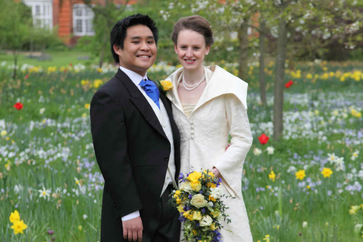 A bride and groom in Newnham's gardens