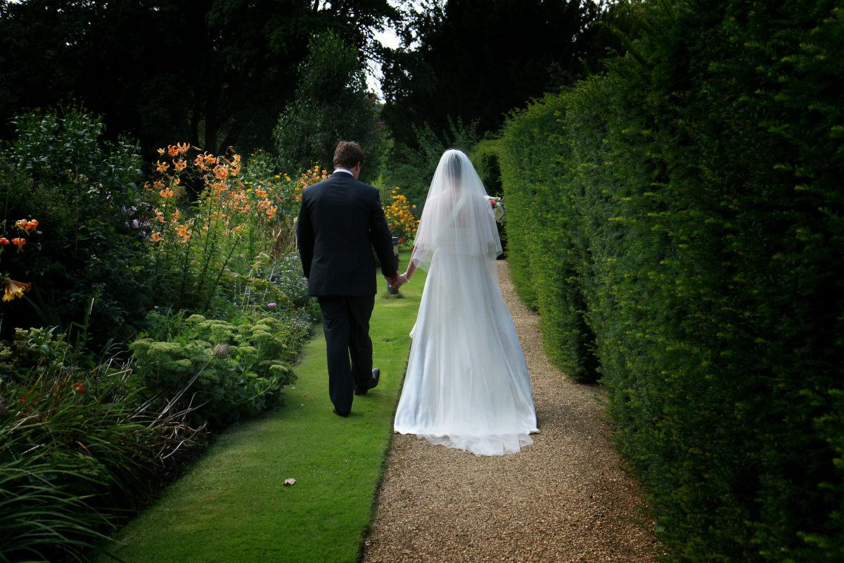 Bride and groom walk through Newnham gardens