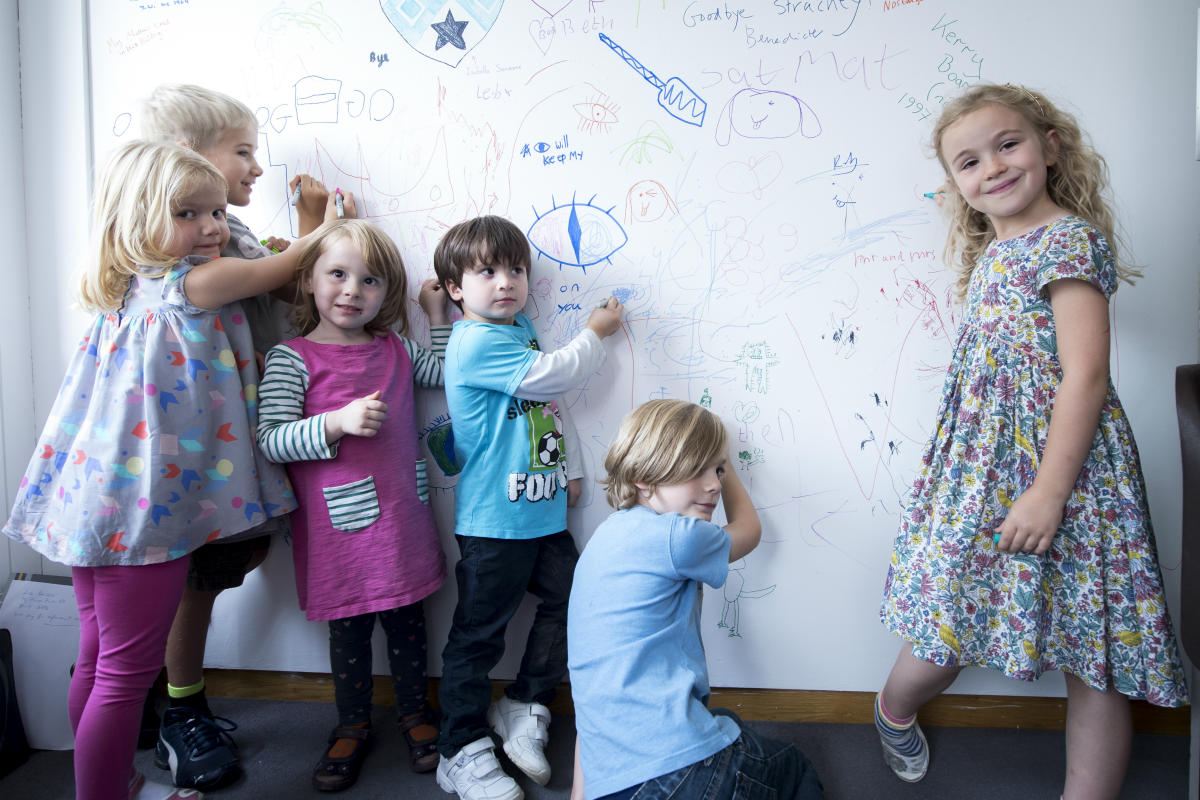 Children drawing on the walls in the graffiti room
