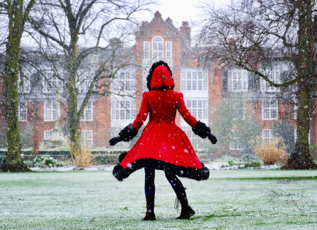 A person in a red coat, fringed with black faux-fur is in the middle of a twirl on a snowy, grassy lawn. The building of Peile is visible in the background through snowflakes falling.