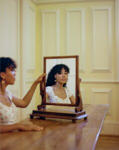 A portrait of a student looking into a mirror